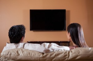 Asian couple watching TV